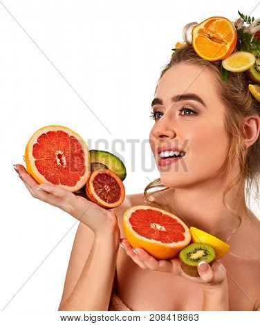 Hair and facial mask from fresh fruits for woman concept Girl with beautiful face holds halves of grapefruit and avocado for homemade organic skin therapy on white isolated Acceleration of hair growth