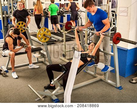 Fitness friends workout gym. Woman working on bench press. She lifting barbell. Man backs girl while taking exercises. Group work people on background. Maintenance of sports form.