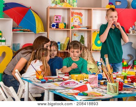 Kids playroom organization of children painting and drawing in kid's club. Craft lesson in primary school. They learn to live in a team. Boys at drawing lesson. Kid boy coloring picture in class.