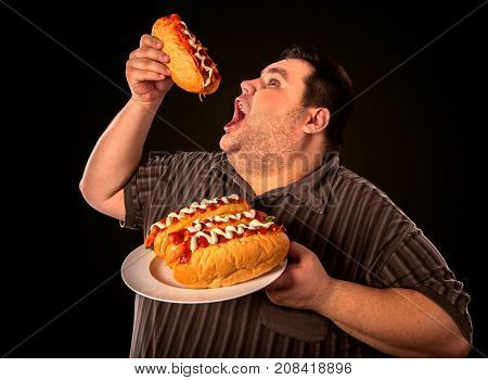 Diet failure of fat man eating fast food hot dog on plate. Breakfast for overweight person who greedily eats lot. Use of semi-finished products for food. Enraged by large amount of food fat.