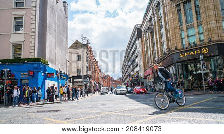 DUBLIN IRELAND - AUGUST 10 2017; People waiting and crossing busy city intersection with shop brands and signage on both sides as cyclist rides through ahead of change of lights.