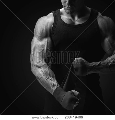 Croped Shot Of Strong Man Wrap Hands On Black Background Man Is Wrapping Hands With Boxing Wraps Iso