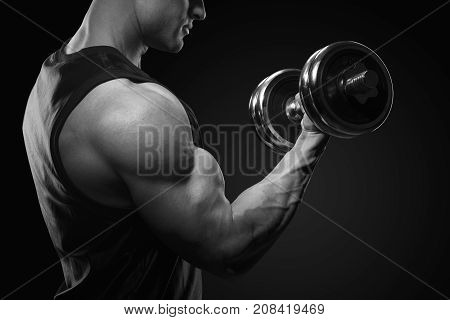 Black And White Photo Of Handsome Power Athletic Man In Training Pumping Up Muscles With Dumbbell. C
