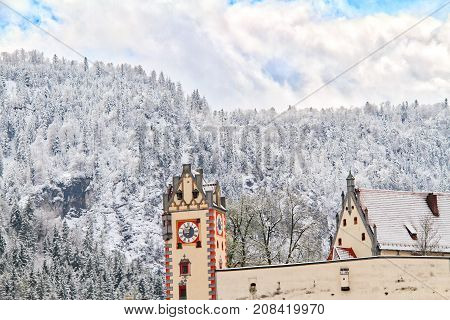 A snow covered mountain in Fussen, Germany with a classical German building in the foreground.