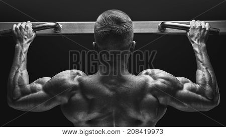Close-up Photo Of Attractive Muscular Bodybuilder Guy Doing Pullups In Gym. Fitness Man Pumping Up L