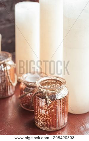 White Christmas candles and a glass jar with rustic twine standing onwindow sill. New Year eve