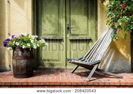 Old fashioned porch decorated with wooden chair and bucket with flowers