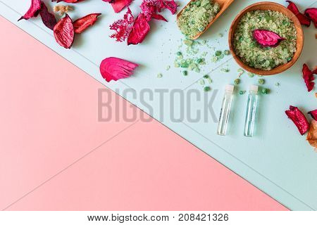 Aroma therapy and a face scrub and bodies of green salt on a blue and pink background. Top view