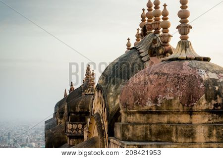 Domes and spires of a hindu fort temple with jaipur city visible in the distance. The oldness of the building is shown through the wear and discoloration of the building. However the carvings and detailings are still perfect