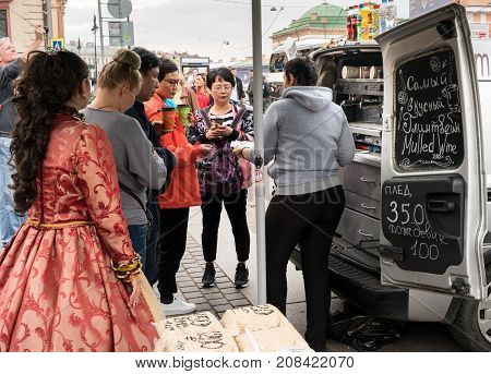 ST PETERSBURG, RUSSIA - SEPTEMBER 12: Tourists get coffee from street vendor on September 12, 2017 in St Petersburg, Russia. Tourists can stay for 3 days without a visa.