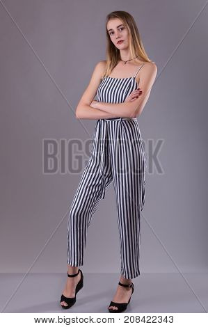 Confident attractive slender young woman wearing striped overall standing with folded arms looking thoughtfully at the camera over gray studio background with copy space