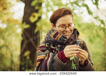 cute happy girl in glasses with a sweatshirt and a scarf found in the forest blueberries and wants to eat it. autumn forest berries and people. focus on blueberries in hands.
