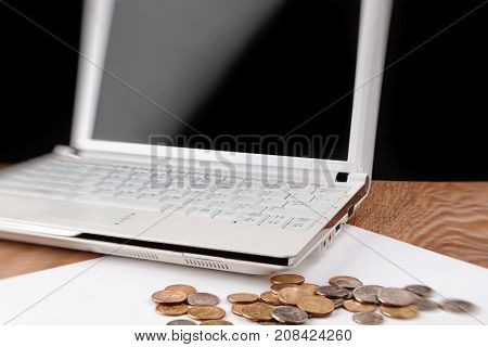 Laptop with blank screen and heap of coins on wooden table. Selective focus and partial blur