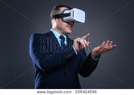 In virtual reality. Delighted nice smart man holing an invisible object and using it while being in a virtual reality