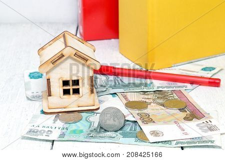 Wooden house and Russian money on the background of business folders. Payment of tax