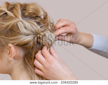 Beautiful blonde girl with a beautiful neat hairstyle close-up in a beauty salon. Professional hair care and creating hairstyles.