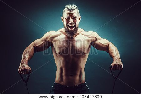 Fitness man exercising with stretching band in studio. Bodybuilder workout. Fitness, exercise and healthy lifestyle.