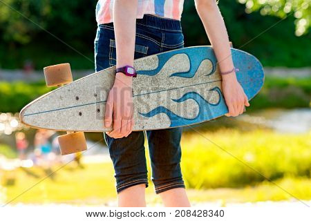 Young skateboard girl holding her longboard outdoors on sunset. Hipster girl with skateboard