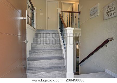 Small Foyer Design Boasts A Gray Wood Staircase