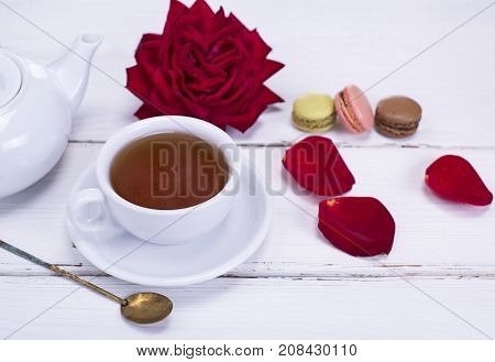 black tea in a white round cup with a saucer on the table next to a white tea pot