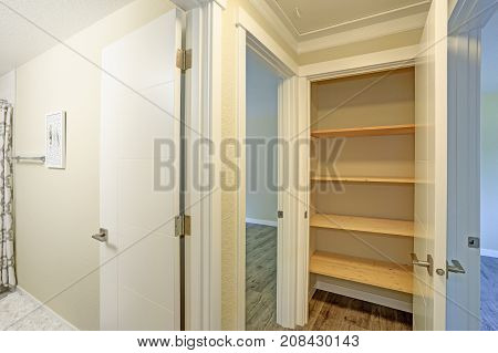 White Door Opens To A Kitchen Pantry Filled With Wooden Shelves