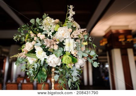 Stylish and elegant bouquet of lovely flowers as an indoor decoration in the bright restaurant hall