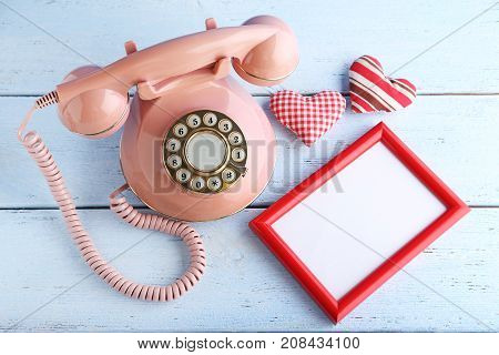 Pink Retro Telephone With Photo Frame And Hearts On White Wooden Table