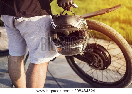 Young man biker with protective helmet in hand standing near electric bike. Ebike bicycle environmentally friendly eco e-mountainbike transport. Healthy lifestyle