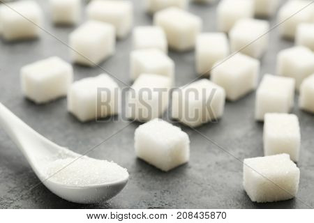 Sugar Cubes With White Spoon On Grey Wooden Table