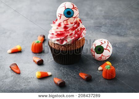 Halloween Cupcake With Candies On Grey Wooden Table