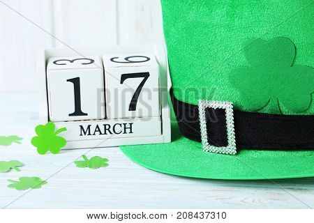 Green Paper Clover Leafs With Calendar And Hat On White Wooden Table
