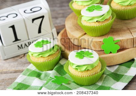 Delicious Cupcakes With Clover Leaf On Grey Wooden Table