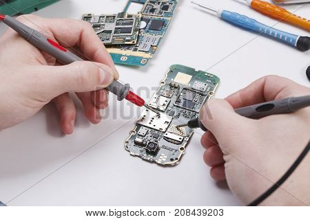 Repairing smartphone with multimeter close up. Technician pov, broken phone diagnostics at service center, repairman workplace