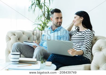 Love you to the moon and back. Loving young man and woman looking at each other with smiles on their faces while both sitting on a sofa and working together indoors.
