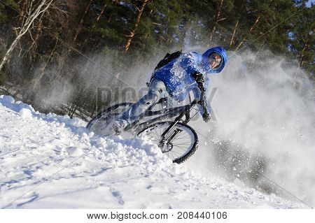 Extreme cyclist riding bicycle near snowbanks of mountain slope, winter sport