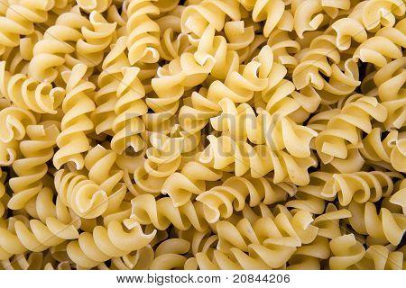 Raw spiral pasta noodles closeup macro
