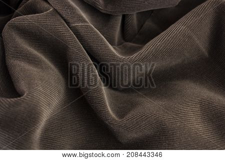 Photo of a brown, folded, striped, velvet.