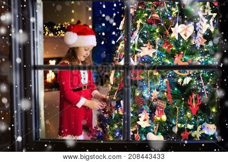 Child At Christmas Tree. Kid At Fireplace On Xmas Eve