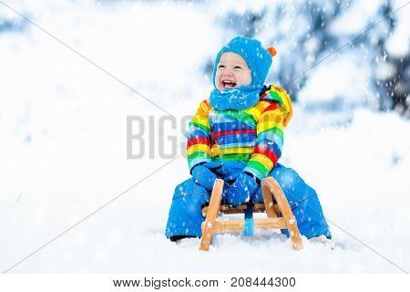 Boy On Sleigh Ride. Child Sledding. Kid With Sledge