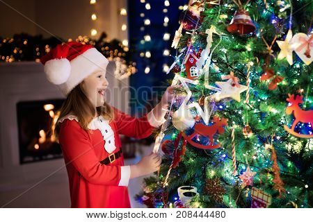 Child At Christmas Tree And Fireplace On Xmas Eve