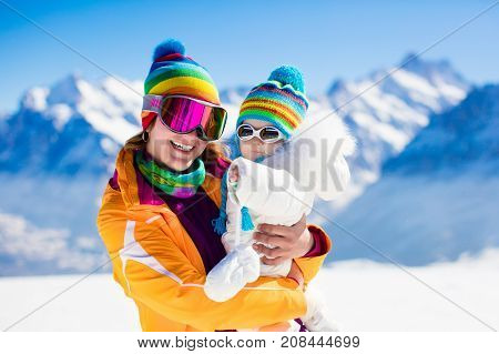 Young mother and little baby enjoying winter ski vacation in alpine resort. Eyewear and sun protection sunglasses for infants. Family with safe goggles walking in the snow in the Alps mountains.