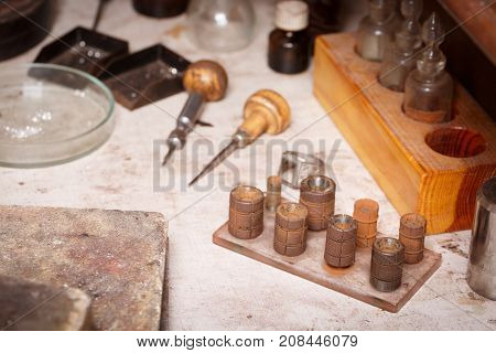 Close-up of professional tools for jewelry making on a workshop table background. Manufacture of jewelry accessories with equipment.