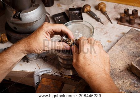 Close-up of a man's hand manufacturing jewellery accessories on a workshop background. Craft jewelry making with professional tools.