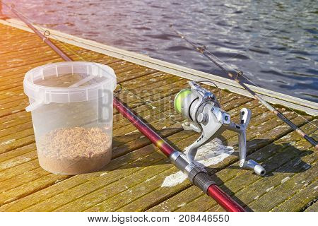 Fshing rod and bucket of bait on the wooden pier