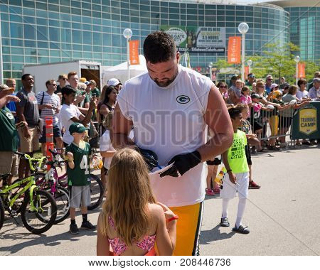 Green Bay WI - August 1 2017: Green Bay Packer Kyle Murphy signing autograph for young fan after football practice. The community owned team has a long tradition of player involvement with fans.
