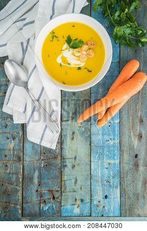 Carrot soup with cream and parsley on wooden background. Top view. Copy space