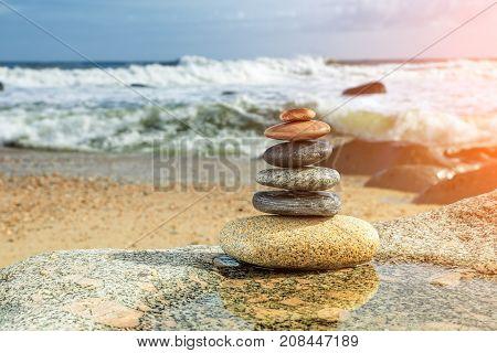 Zen Balancing Pebbles on sunny Beach background