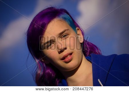 Girl with extreme hair on blue sky background