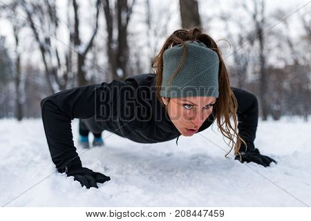Female Athlete Exercising In Park In Winter, Color Image