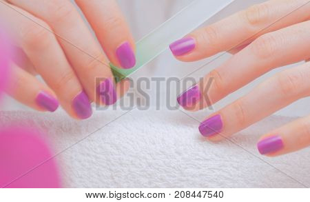 Female hands making nail manicure on a towel